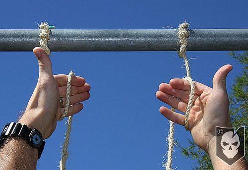 Man folding the two ropes in his hands.