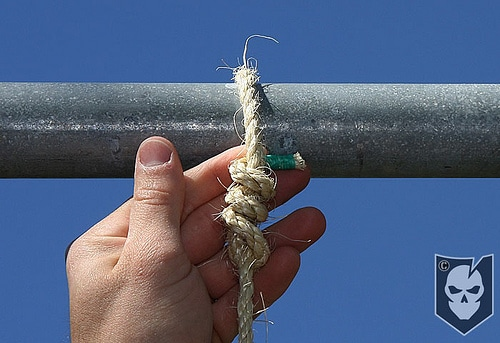 Man tighten the rope with pipe and securing each strand.