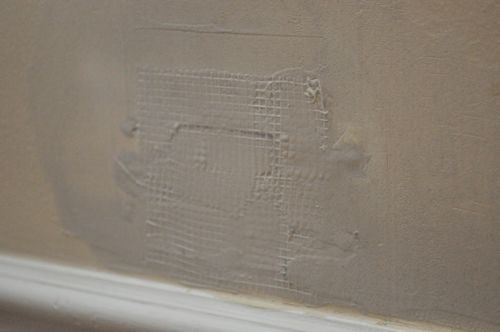 Smoothing the compound on drywall.