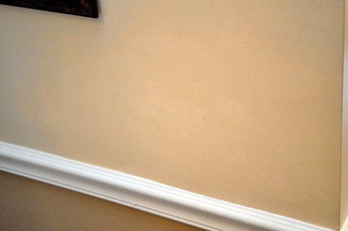 Applying paint on drywall.