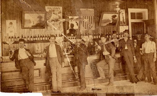 vintage saloon late 1800s men posing in front of bar