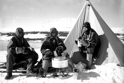 Men cooking food at the top of snowy mountains.