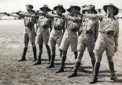 Men wearing shorts during gun shoot practicing.