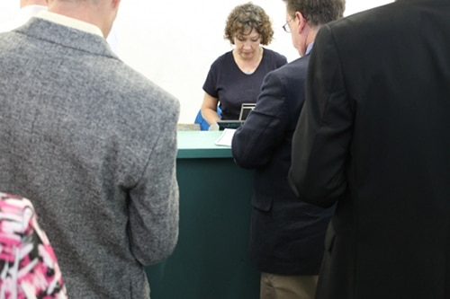 Men purchasing tickets from woman for horse racing.