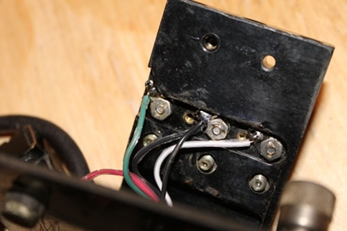 Vintage connecting new wires to terminals on top plate.
