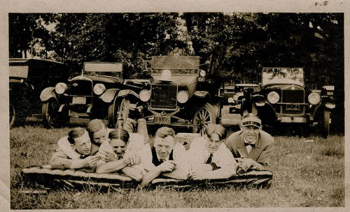 Vintage peoples are laying front of vehicles black and white photo illustration.