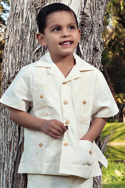 Young boy wearing beige tan guayabera shirt.