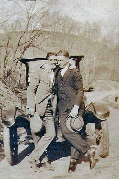 Vintage two men standing front of vehicle and holding hats black and white illustration.