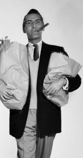 vintage man holding bags of groceries smoking cigar.