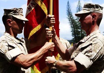 Marines holding flag shirt sleeves rolled above elbow.