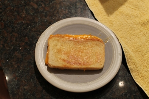 Vintage grilled cheese sandwich over a plate.