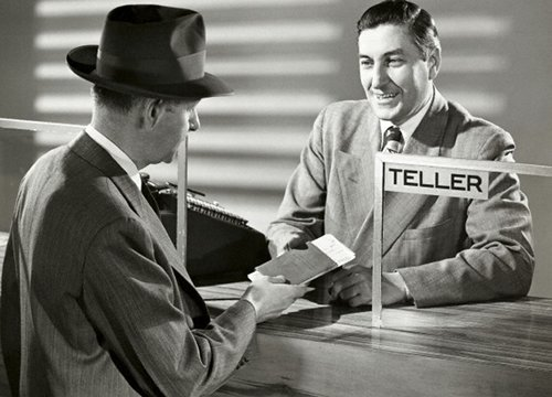 Vintage bank teller helping customer.