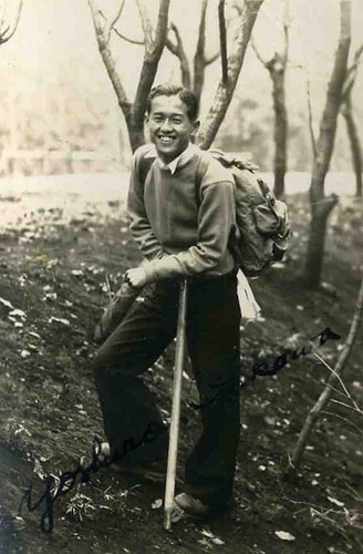 Vintage Asian man hiking outdoors having walking stick.