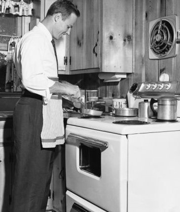 Vintage man cooking on stove smiling.