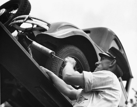 Vintage man working on car shirt sleeves rolled above elbow.