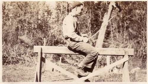 vintage young man sitting on wooden sawhorse