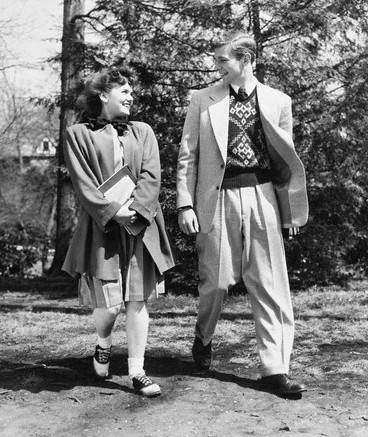 Vintage young man and woman walking outdoors talking smiling.
