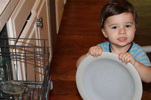 Young boy doing chores holding plate emptying dishwasher.