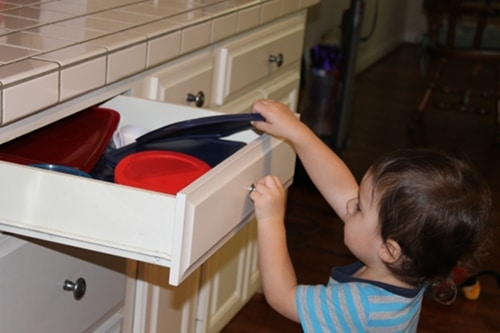 young boy doing chores putting dishes away kitchen