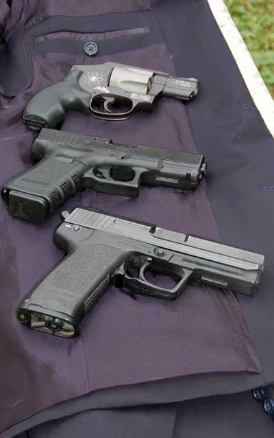 Handguns lying on blazer concealed carry weapon.