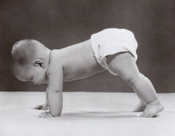 Vintage baby in diaper on hands and feet crawling.