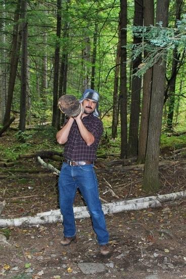 Vintage man hoisting log lengthwise onto his right shoulder.
