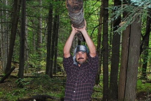 Vintage man lift the log above his head.