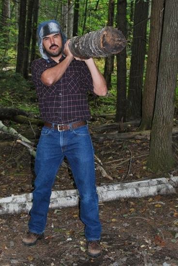 Vintage man lower the log onto his left shoulder.