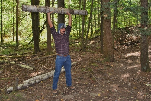 Vintage man pressing the log over his head.
