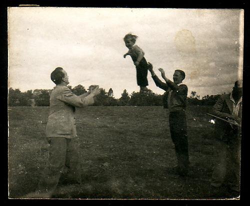 Vintage men tossing young boy between them.