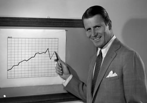 Vintage businessman smiling and drawing line graph chart on board.
