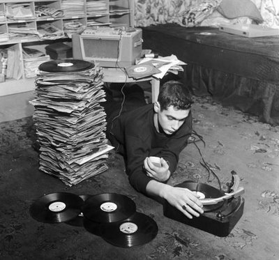 young man lying on floor stack of records and vinyl player