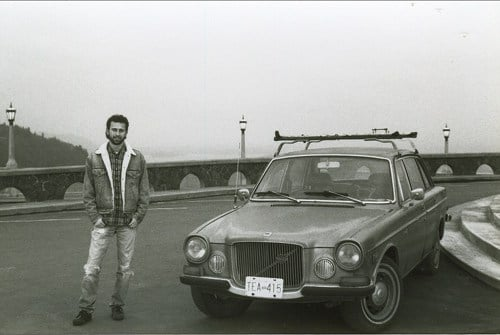 vintage man with older volvo car on bridge