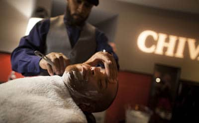 Master barber Charles Lennox of haberdash men on location giving demonstration of shave.
