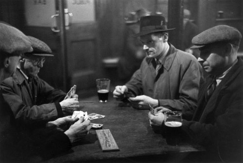 vintage men playing cribbage in bar with beer flat caps