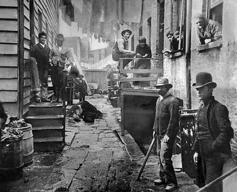Vintage gang of working class men in alleyway.