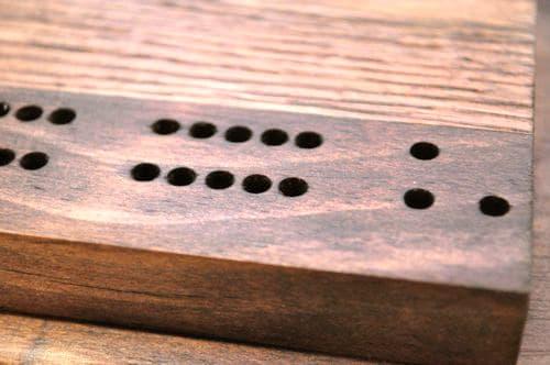 DIY wooden cribbage board having holes.