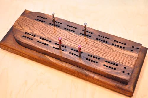 DIY wooden cribbage board having holes and nails in it.