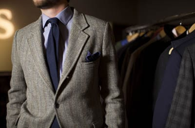 Male model wearing grey blazer blue tie button up shirt.
