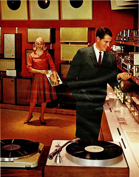 Turn table playing music man and women standing women holding record in a pleasant mood.