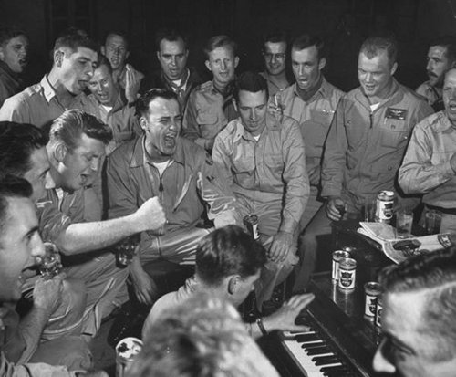 soliders at a bar singing man playing piano