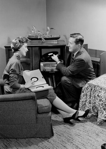 Man and women chatting in pleasant mood and selecting records for turn table.