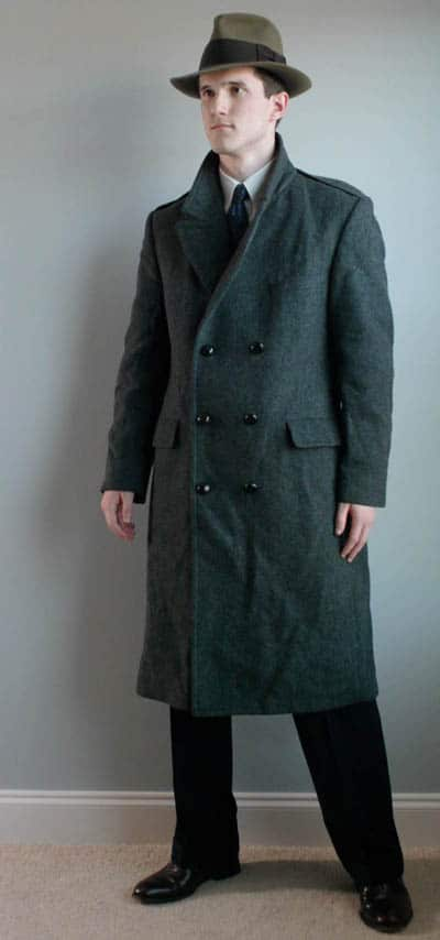 Male model wearing dark green overcoat with fedora hat and dark trouser.
