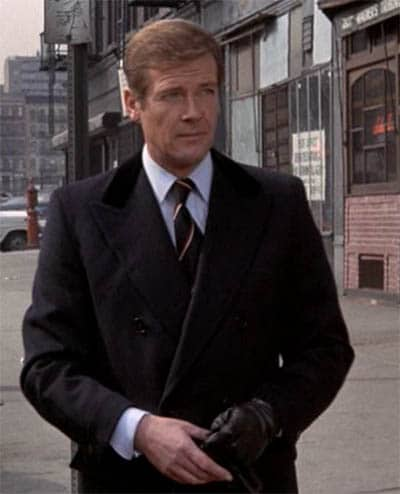 James Bond Roger Moore outdoors wearing black overcoat.