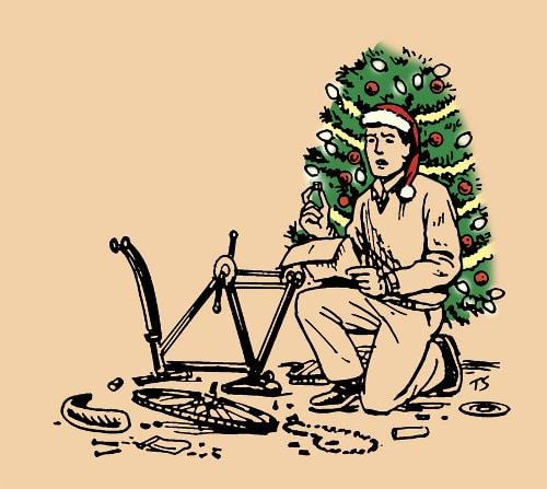 Man in santa hat assembling bicycle beside Christmas tree.