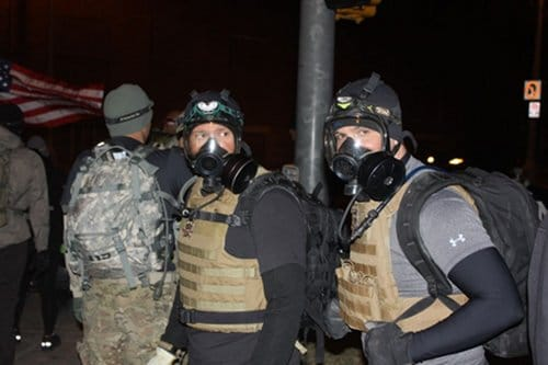 Guys from Blue Line Tactical Fitness wear gas masks.