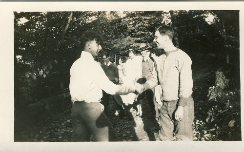 vintage young men shaking hands smiling
