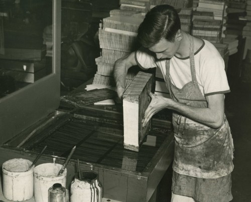 Vintage apprentice young man binding printed books.