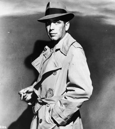Vintage detective wearing trench coat fedora and cigarette.