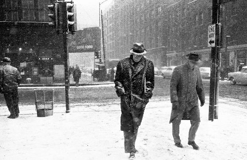 vintage men waking in snowstorm in city wearing fedoras